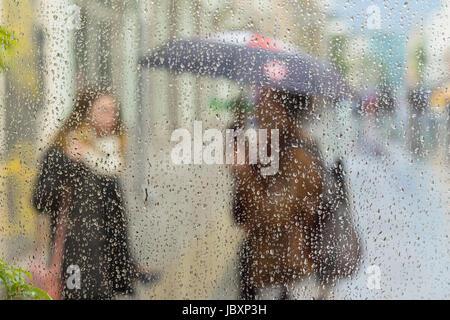 Abstrakte verschwommene Silhouetten von Menschen mit Regenschirmen an regnerischen Tag in der Stadt, zwei Mädchen - Stockfoto