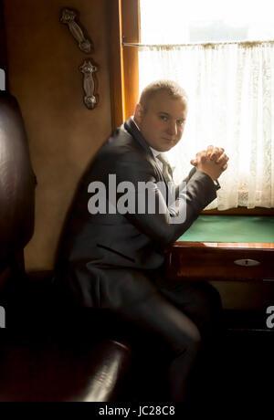 Porträt von eleganten Geschäftsmann Reisen in alten Zug getönt - Stockfoto