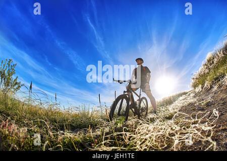 Niedrigen Winkel Ansicht des Radfahrers stehend mit Mountain-Bike unterwegs bei Sonnenaufgang. - Stockfoto