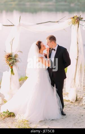 Das Full-length Foto des glücklichen Brautpaares während der Hochzeitszeremonie in der Nähe des Flusses. Die Braut - Stockfoto