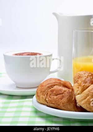 Eine Einstellung der Frühstück Croissant, Orangensaft und Kaffee auf einer grünen karierte Tischdecke. - Stockfoto
