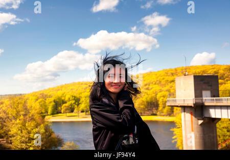 Eine Chinesin mit ihrem Haar wehen außer Kontrolle auf der Seeseite der Hop Brook Dam in Naugatuck Connecticut an - Stockfoto