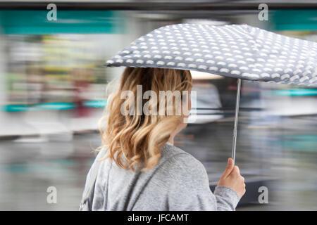 Verschwommen Menschen mit Sonnenschirmen auf der Stadtstraße an einem regnerischen Frühlingstag - Stockfoto