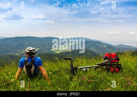 Rückansicht des Mannes entspannen auf dem Rasen und mit Blick auf Berge - Stockfoto