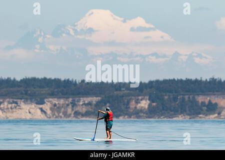 Paddle boarding am Puget Sound mit Mount Baker im Hintergrund stand. - Stockfoto