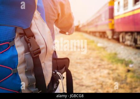Junge Hipster Mann mit einem Rucksack bereit, eine Reise mit dem Zug, trendigen Mann stehend wegsehen. - Stockfoto