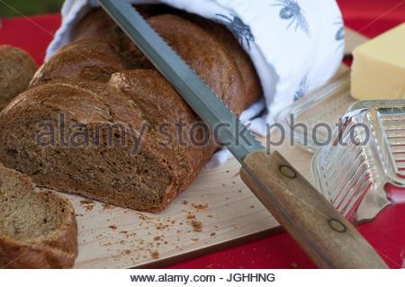 Geflochtene Laib Schwarzbrot auf Schneidebrett außerhalb mit Wellenschliff und Butter auf roten Tischdecke. - Stockfoto