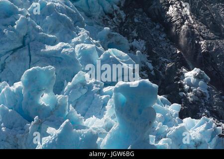 Blaues Gletschereis drückt gegen die schwarzen Felsen bröckelt - Stockfoto