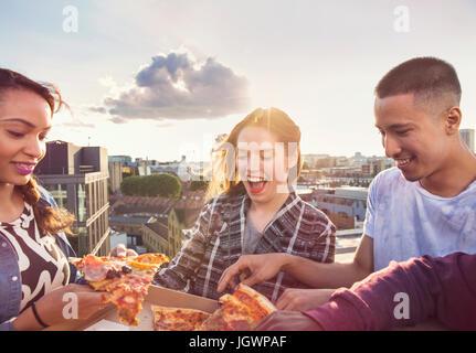 Jungen Erwachsenen Freunden teilen Pizza bei Dach-Party in London, UK - Stockfoto