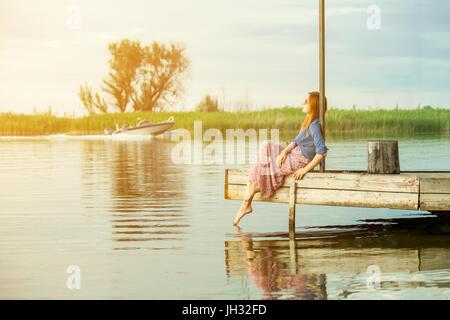 Schöne junge rote behaarte Mädchen in bunten lange Sarafan Kleid sitzt auf einem hölzernen Pier auf einem Fluss - Stockfoto