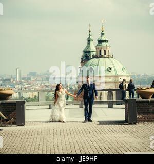 Das Full-length Foto das glückliche Brautpaar Hand in Hand während des Gehens auf dem Hintergrund der Prager Dom. - Stockfoto
