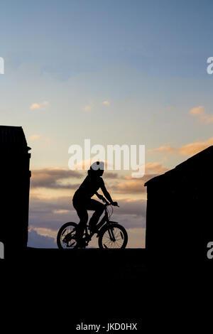 Silhouette der Mädchen auf dem Fahrrad - Stockfoto