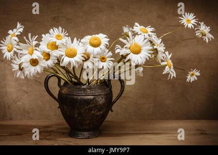 Vintage Vase Metall - Stillleben Gänseblümchen. Kunst Stil Kamille-blühende Blumen, wunderbare Dekoration des Innenraums. - Stockfoto