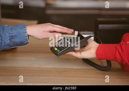 Nahaufnahme von Frau Zahlung Rechnung durch Smartphone mit NFC-Technologie im café - Stockfoto