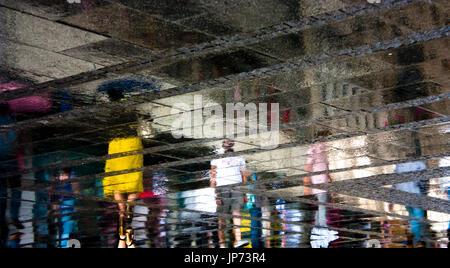 Verschwommen Reflexion Schatten Silhouetten von einzelnen Menschen zu Fuß auf einem regnerischen und sonnigen Stadt - Stockfoto