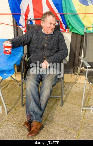 Ältere männliche außerhalb eines Shop mit einem Becher in seinen Händen an einem Winter sitzen. - Stockfoto
