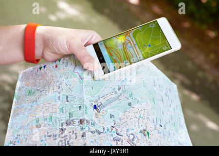 Smartphone mit GPS-Navigator und Karte in den Händen eines Touristen - Stockfoto