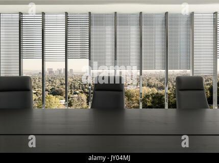Leere Stühle am Schreibtisch im Büro Zimmer gegen teilweise überdachten Fenstern mit Stadtbild im Hintergrund - Stockfoto