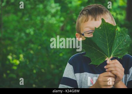 Ein kleiner Junge hält ein grünes Blatt vor seinem Gesicht. - Stockfoto