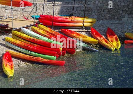 Bunte Kanus auf dem Wasser. Rote und gelbe Kajaks bereit für den Sommer Aktivitäten und Erholung. - Stockfoto