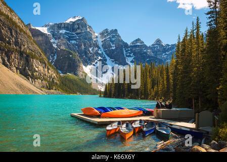 Kanus auf einem Steg am Moraine Lake im Banff Nationalpark, Alberta, Kanada, mit Schnee bedeckten Gipfeln der kanadischen - Stockfoto