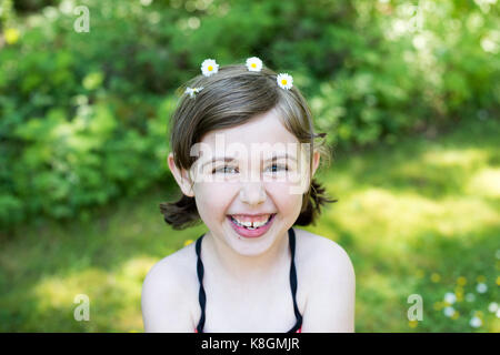 Porträt eines jungen Mädchens im Freien, das Tragen von Gänseblümchen in Haar, lächeln - Stockfoto