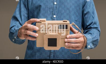 Fotograf mit einem handgefertigten umweltfreundlichen Karton Kamera, Handwerk und Kreativität Konzept - Stockfoto