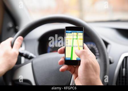 Close-up des Menschen mit Hilfe der gps-Navigation im Handy während der Fahrt Auto - Stockfoto
