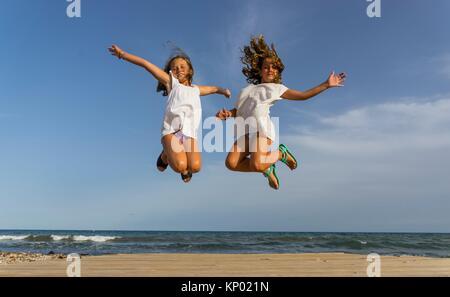 Mädchen spielen, springen am Strand, Alcocebre, Spanien. - Stockfoto