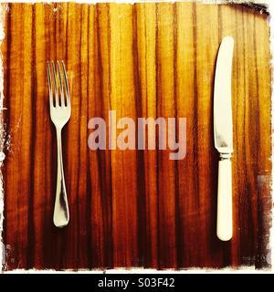 Messer und Gabel auf poliert sehr stilvolle Holzmaserung retro 60er Esstisch - Stockfoto