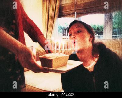 Frau auf einer kleinen Geburtstagstorte Kerzen ausblasen - Stockfoto