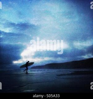Eine Surfer kommt am späten Abend Surfen im Watergate Bay Strand. Newquay, Cornwall, England UK. - Stockfoto