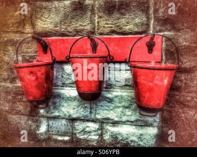 3 rote Sand und Wasser Eimer von Halterungen an der Wand hängen - Stockfoto