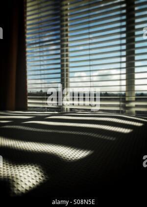 Fenster-Venetian blinds Schattenwurf auf Bett - Stockfoto