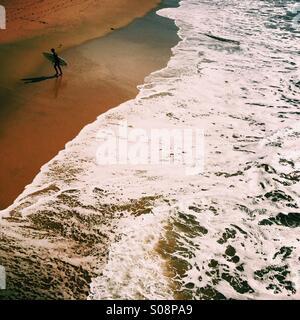 Eine männliche Surfer geht bis zum Strand. Manhattan Beach, Kalifornien USA. - Stockfoto