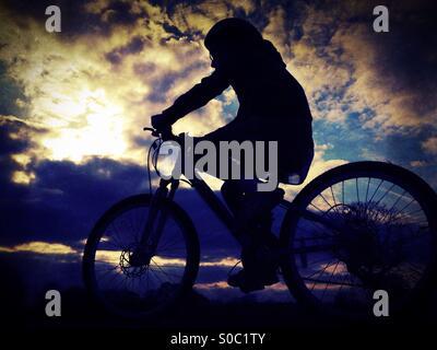 Junges Mädchen auf dem Fahrrad in der Silhouette gegen dramatischer Himmel - Stockfoto