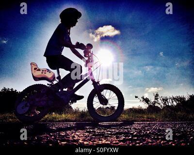 Junges Mädchen mit ihrem Fahrrad in Silhouette gegen die Sonne - Stockfoto