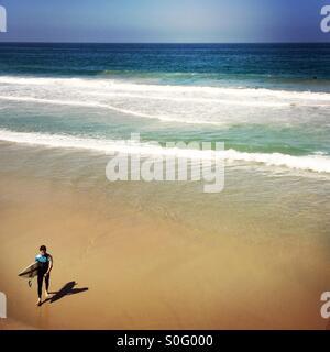 Eine männliche Surfer geht bis zum Strand. Manhattan Beach, Kalifornien. USA. - Stockfoto