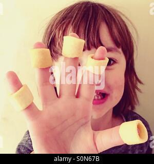 Kleinen 4-jährigen Jungen mit Kartoffelchips an seinen Fingern. - Stockfoto