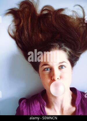 Frau mit verrückten Haar weht eine Kaugummi-Blase - Stockfoto