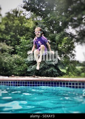 Mädchen tragen lila Anzug und Schwimmbrillen in einen Pool springen - Stockfoto