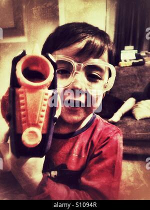 Ein kleiner Junge tragen Schutzbrillen, spielen mit einer Spielzeugpistole. - Stockfoto