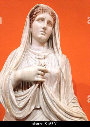 Klassische Marmorstatue eines römischen Mädchens mit orangem Hintergrund. - Stockfoto