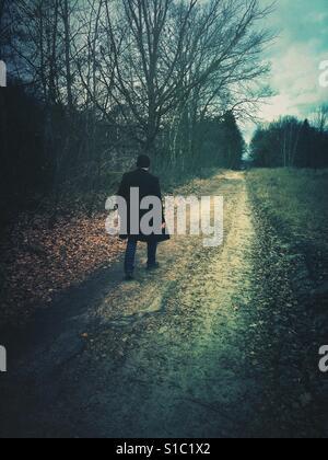 Rückansicht eines Mannes trägt einen Mantel zu Fuß entfernt, auf einer Land-Straße - Stockfoto