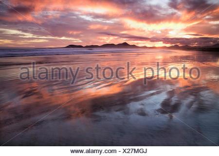 Sonnenuntergang reflektieren über Strand von Famara, Lanzarote, Kanarische Inseln, Spanien, Europa - Stockfoto