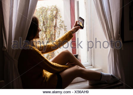 Junge Frau, die eine Selfie am Fenster - Stockfoto