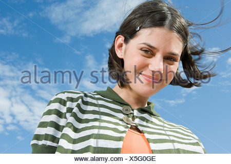 Lächelndes Mädchen gegen blauen Himmel - Stockfoto