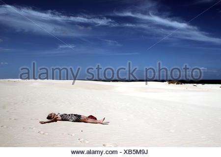 Spanien, Kanarische Inseln, Fuerteventura, Natur Park der Dünen von Corralejo, Frau liegt in der Wüste - Stockfoto