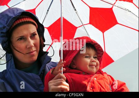 La madre y el bebé bajo un paraguas mirando la caída de lluvia en un día de invierno . Foto de stock