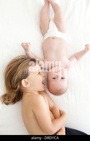 Hermana besando a su hermano más joven Foto de stock